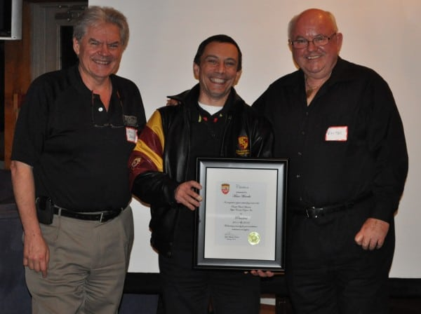 Past President Mario Marrello was recognized by the club for his service with a Porsche jacket and framed certificate of gratitude. Mario (centre) is congratulated by director Del Bruce and president Walter Murray at the social.