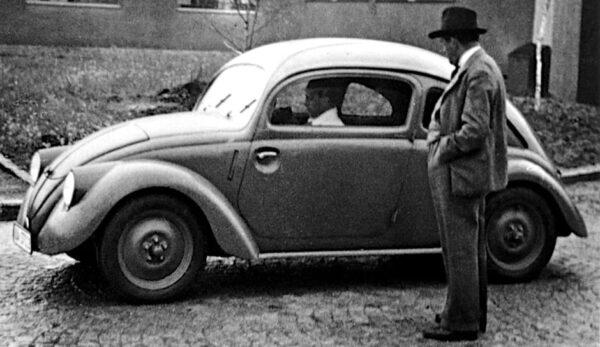 Ferdinand Porsche with an early Beetle prototype. Copyright Porsche